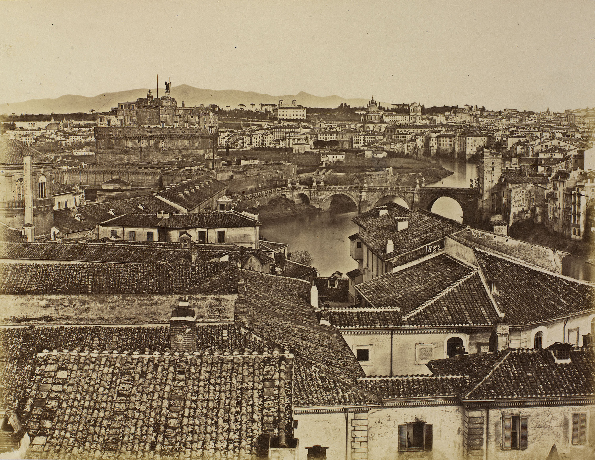 Photograph of a view of Rome with the bridge of St Angelo spanning the river Tiber in the middle distance and the Sabine Hills in the far distance. Roof tops of buildings dominate the foreground.