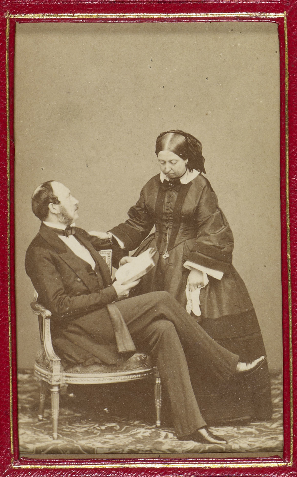 Carte-de-visite photograph of Queen Victoria (1819-1901) and Prince Albert, Prince Consort (1819-61). The Queen stands and looks down. Prince Albert is seated, facing right, and holds a book. He gazes up at Queen Victoria.