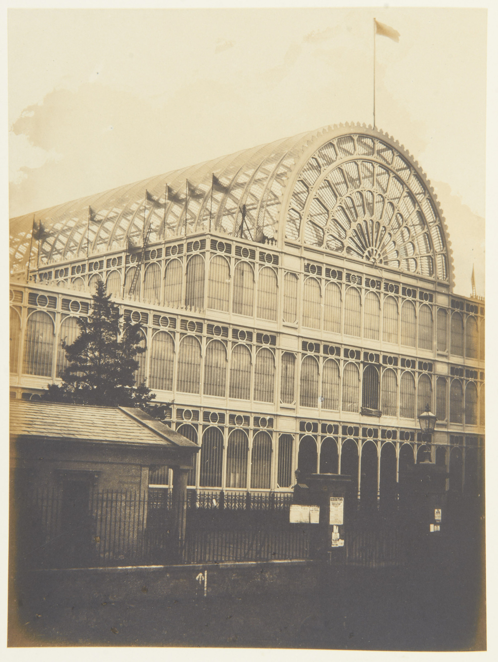 Photographof anexternal view of the south transept of the Crystal Palace, Hyde Park during the Great Exhibition.Flags fly along the building and top ofthe arched roof. <br><br><p>This photograph is from Volume II (RCIN 2800001)