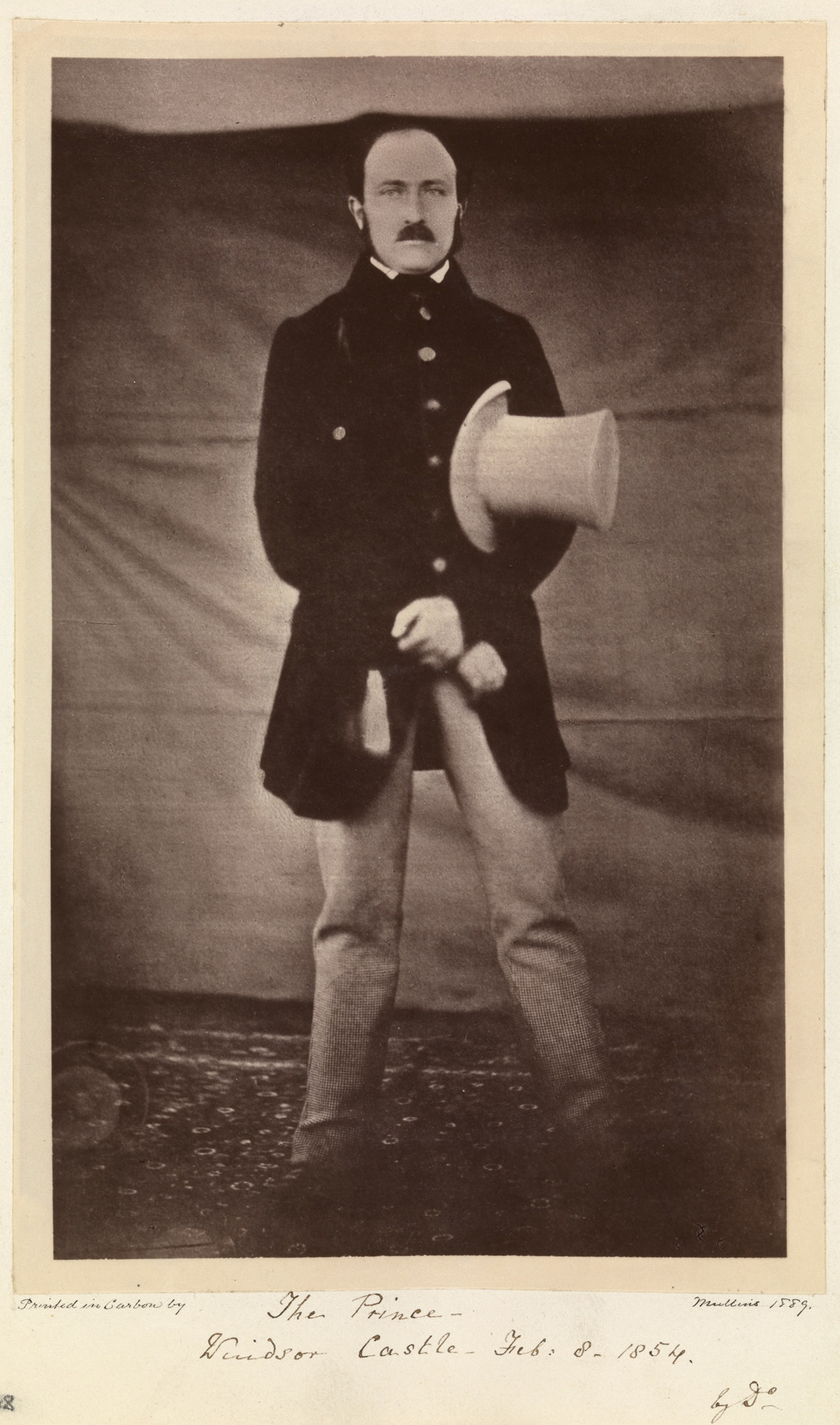 Photograph of a full length portrait of Prince Albert (1819-61) standing, facing the camera front on. He poses with his arms crossed in front of his body. He holds a light colour top hat under his left arm. Photograph taken at Windsor Castle.