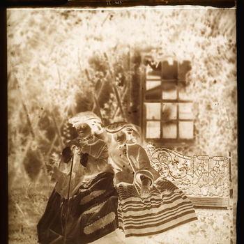 Glass plate negative of a full length portrait of Victoria, PrincessRoyaland Princess Alice. The sistersare seated together on a decorative ironwork garden seat. The Princess Royal holds a walking stick with Princess Alice leaning on her