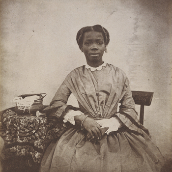 Photograph showing a three-quarters length portrait of Sally [Sarah] Bonetta Forbes, facing the viewer, seated and resting her right arm on a cloth-covered table. The portrait was captioned in the 19th century in ink 'Sally Bonetta Forbes' and dated 1856.