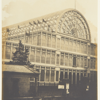 Photograph of an external view of the south transept of the Crystal Palace, Hyde Park during the Great Exhibition. Flags fly along the building and top of the arched roof. <br><br><p>This photograph is from Volume II (RCIN 2800001)