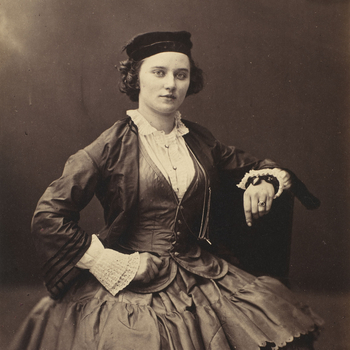 Photograph of a three-quarter length portrait of a woman, facing towards the viewer.She rests her left arm on the back of a chair and her right hand on her right hip. The woman wears a dark colour hat, light colour shirt, dark colour, fitted shirt,