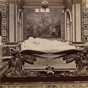 Photograph of Prince Albert's tomb inside the Royal Mausoleum, Frogmore, in the Home Park, Windsor. The Prince's effigy is supported by winged angels and a single wreath lies against the side of the tomb. In the background, set against marble walls, porti