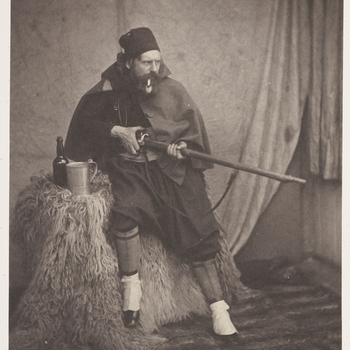 Photograph of Roger Fenton (1819-1869) dressed in traditional Zouave costume. He is leaning against a table which is covered by an animal fur, with his right leg raised off the ground. He is facing partly right and is holding a rifle with both hands. He i