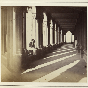 Photograph showing view of an open corridor at Osborne House, Isle of Wight. Prince Arthur, later Duke of Connaught (1850-1942) is seated on a ledge, on the left side of the photograph.