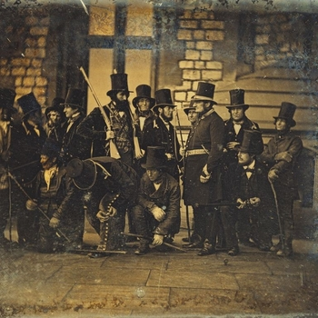 Photograph showing assorted members of the Royal Household keepers and beaters standing around in their uniforms