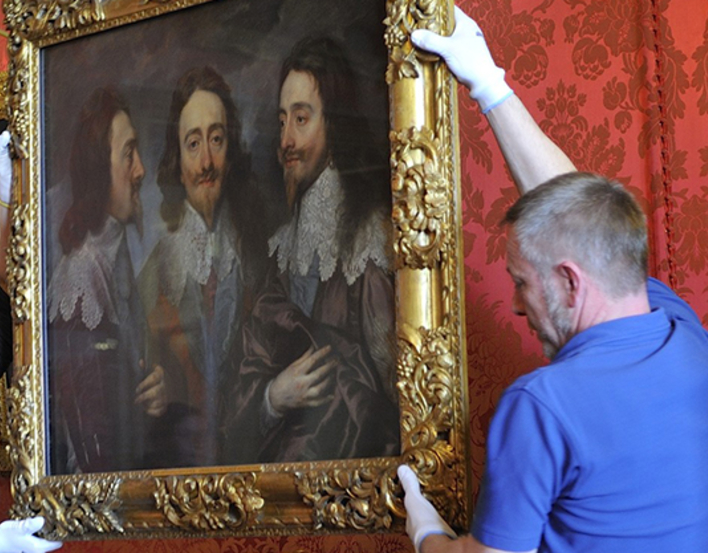 Painting being  moved by art handlers
